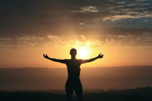 victorious person arms in the air at sunrise ready to take on the day